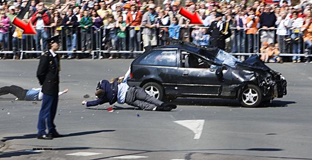 Politie-agenten blijven stoïcijns één kant opkijken, terwijl er voor hun neus drie mensen aangereden worden, een auto voorbij scheurt en het publiek gilt.