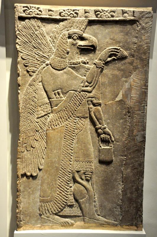 Apkulla, een Soemerische god hier afgebeeld met vogelkop en vleugels. Ook deze figuur houdt maiskolf vast en draagt een 'horloge'/armband en mand in zijn andere hand.