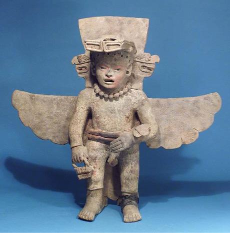 Beeld uit Mexico, tevens met vogelkop en vleugels. Ook deze figuur draagt een mand en een soort horloge/armband.