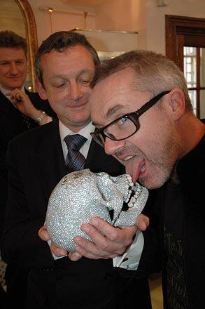 Damien Hirst met een van zijn kunstwerken. Niet alleen de symboliek van de schedels met diamanten, maar ook de wijze waarop hij zich hier laat portretteren, is veelzeggend.
